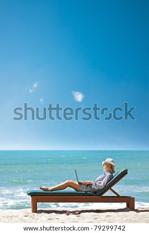 Young woman with laptop on a deck chair at the tropical beach. Vertical shot.