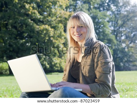 young woman with laptop on a meadow