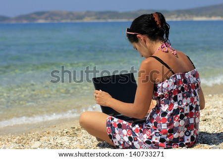 Young woman with laptop on the beach - stock photo