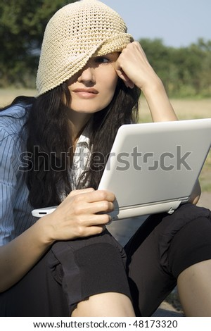 Young woman with laptop sitting in park - stock photo