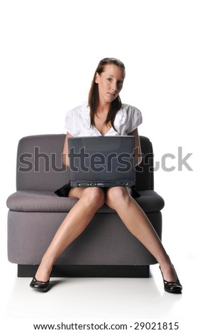 Young woman with laptop sitting on a couch isolated on white