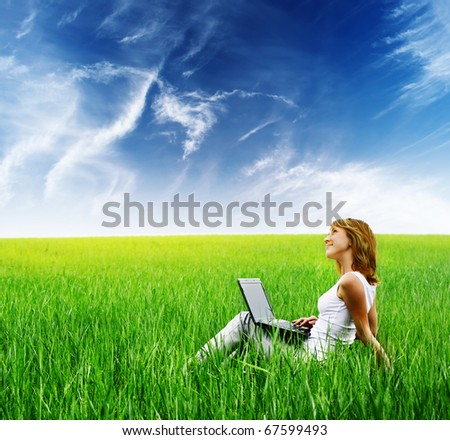Young woman with laptop sitting on green grass - stock photo