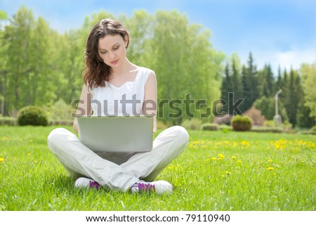 Young woman with laptop sitting on green grass and looking to a display