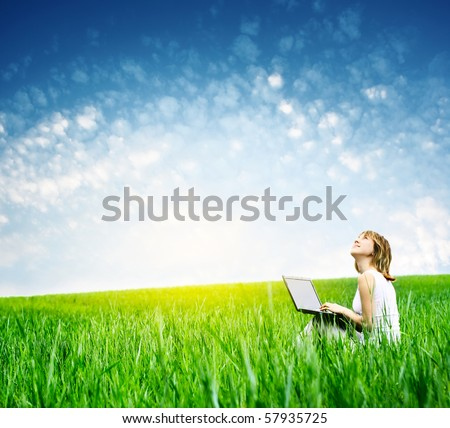 Young woman with laptop sitting on green grass and looking to a sky - stock photo