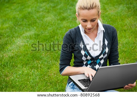 Young woman with laptop sitting on green grass and looking to the screen of laptop - stock photo