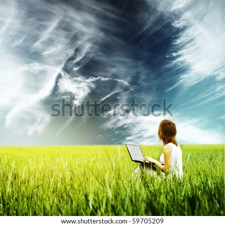 Young woman with laptop sitting on green grass and looking to the sky