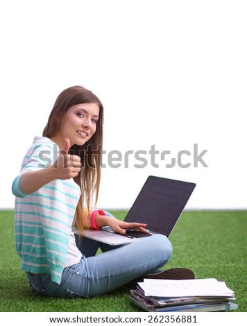 Young woman with laptop sitting on green grass and showing ok. - stock photo