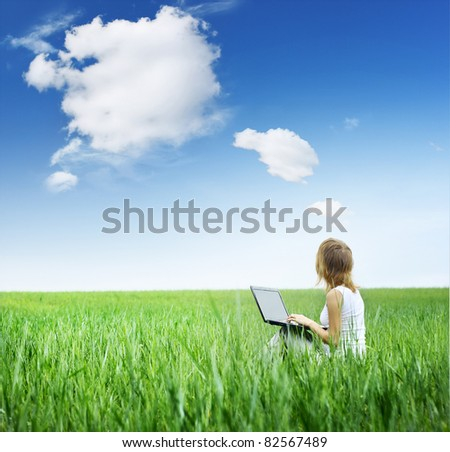 Young woman with laptop sitting on green meadow and looking to a sky with rare clouds