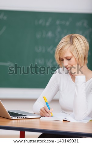 Young woman with laptop writing notes at desk in classroom - stock photo