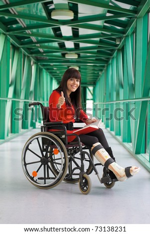 Young woman with leg in plaster after an accident. Sitting in a wheelchair. - stock photo