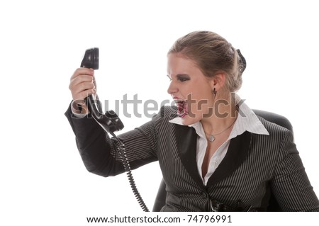 Young woman with lip piercing in a gray business suit and high heels is angry on the phone, isolated on a white background