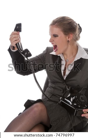 Young woman with lip piercing in a gray business suit and high heels is angry on the phone, isolated on a white background - stock photo