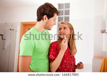 Young woman with lipstick and her boyfriend in the bathroom - stock photo