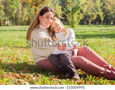Young woman with little girl relaxing in the park. - stock photo