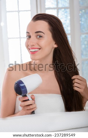 Young woman with long and dark hair drying hair with hairdryer in the bathroom - stock photo