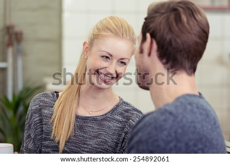 Young woman with long blond hair in a ponytail smiling at a man with love and affection as she listens to him talking, over the shoulder view over the mans shoulder - stock photo