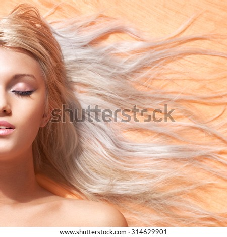 Young woman with long blond hair portrait. Half face composition. - stock photo