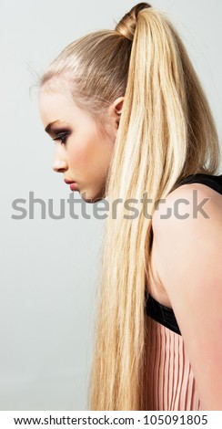 Young woman with long blonde hair in fashion dress in studio in profile - stock photo