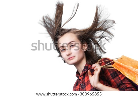 Young woman with long blowing hair and shoping bags isolated on white background with copy-space