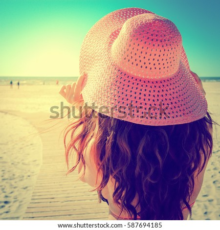 young woman with long brown hair and pink hat, vintage style image