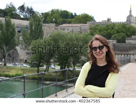Young woman with long brown hair in dark glasses in the ancient French town - stock photo