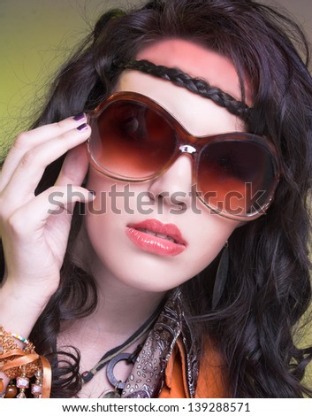 Young woman with long dark hair and in sunglasses posing in hippie image