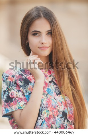 Young woman with long hair outdoors portrait. Soft sunny colors.Close portrait. - stock photo