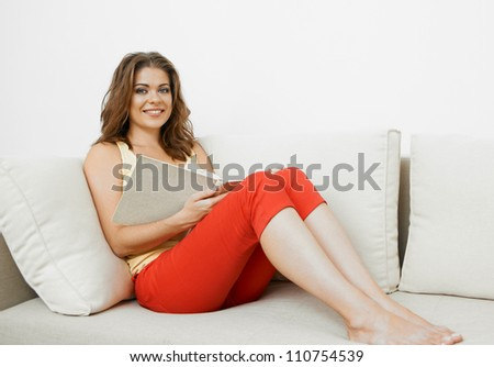 Young woman with long hair sitting  on couch at home with book. - stock photo