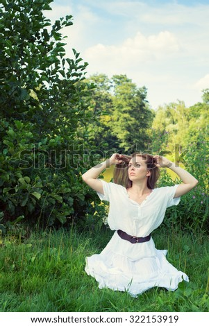 Young woman with long hair sitting on the grass - stock photo