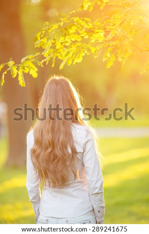 Young woman with long hair turned back  outdoors in sun light Warm Color Tones Beauty Sunshine woman Backlit Sunny Summer Day Autumn Summertime Glow Sun  - stock photo