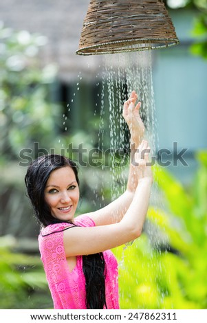 Young woman with long hair under the shower on tropical beach . Sea and water background - stock photo