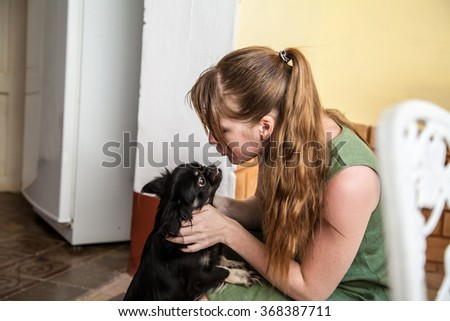 young woman with long red hair in a ponytail sitting and kissing and hugging little black dog puppy with big eyes. Relationships: Love and friendship between animals and humans