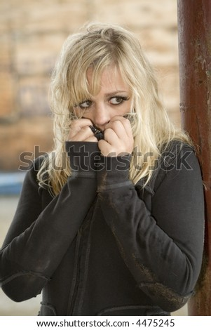Young woman with look of desperation and fear. Hands partially covering face. - stock photo