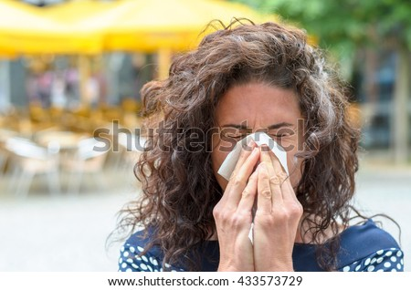 Young woman with lovely long curly hair standing outdoors blowing her nose in an urban square due to a seasonal cold or hay fever