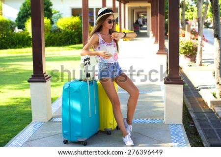 Young woman with luggage at airport,look at her watch,waiting departure.tanned girl with large suitcases,straw hat,sweater,summer sunglasses,denim shorts,happy stylish hipster girl,vintage teen style  - stock photo