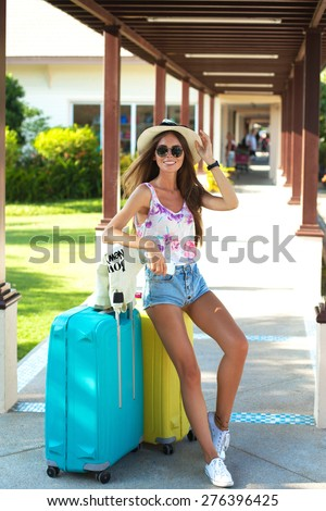 Young woman with luggage at international airport.tanned girl with large suitcases in the airport waiting for departure,holding hat,summer sunglasses,glasses,map,laughing and smiling tropical mood. - stock photo