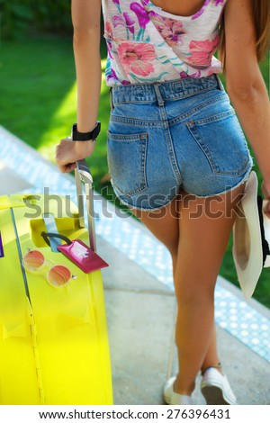 Young woman with luggage at international airport.tanned girl with large suitcases in the airport waiting for departure,holding hat,sunglasses,map,bright summer clothes colors,denim shorts,flower top - stock photo