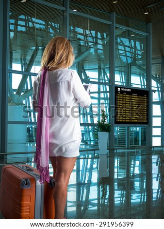 Young woman with luggage at the international airport. - stock photo