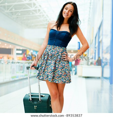 Young woman with luggage at the international airport. She is very happy of her vacation at warm country on christmas holidays