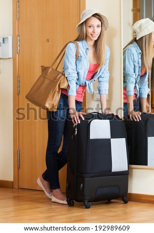 Young woman with luggage staying near door - stock photo