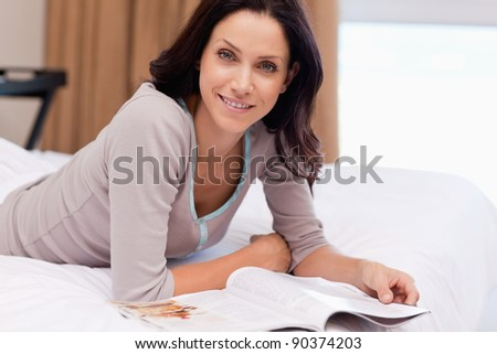 Young woman with magazine lying on the bed - stock photo