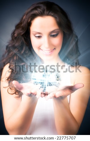 Young woman with magic shine ball. On dark background.