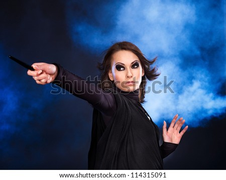 Young woman with magic wand casting spells.