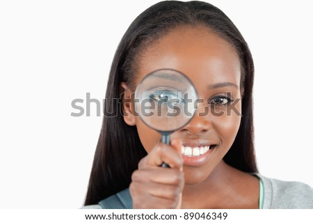 Young woman with magnifier against a white background