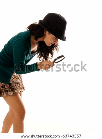 young woman with magnifier glass and hat looking for something isolated on white background - stock photo