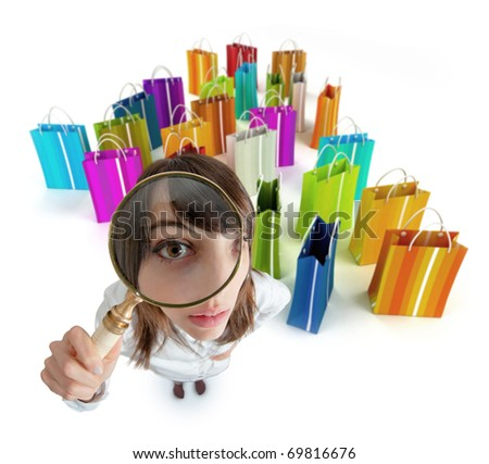 Young woman with magnifying glass with lots of shopping bags - stock photo
