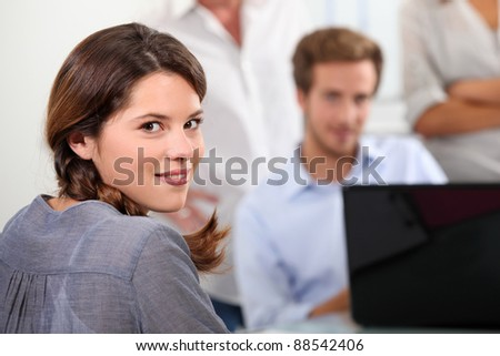 Young woman with male colleagues - stock photo