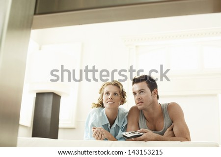 Young woman with man holding remote control in bed - stock photo