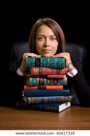 young woman with many book at the desk on black background - stock photo