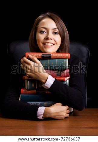 young woman with many books at the desk on black background - stock photo